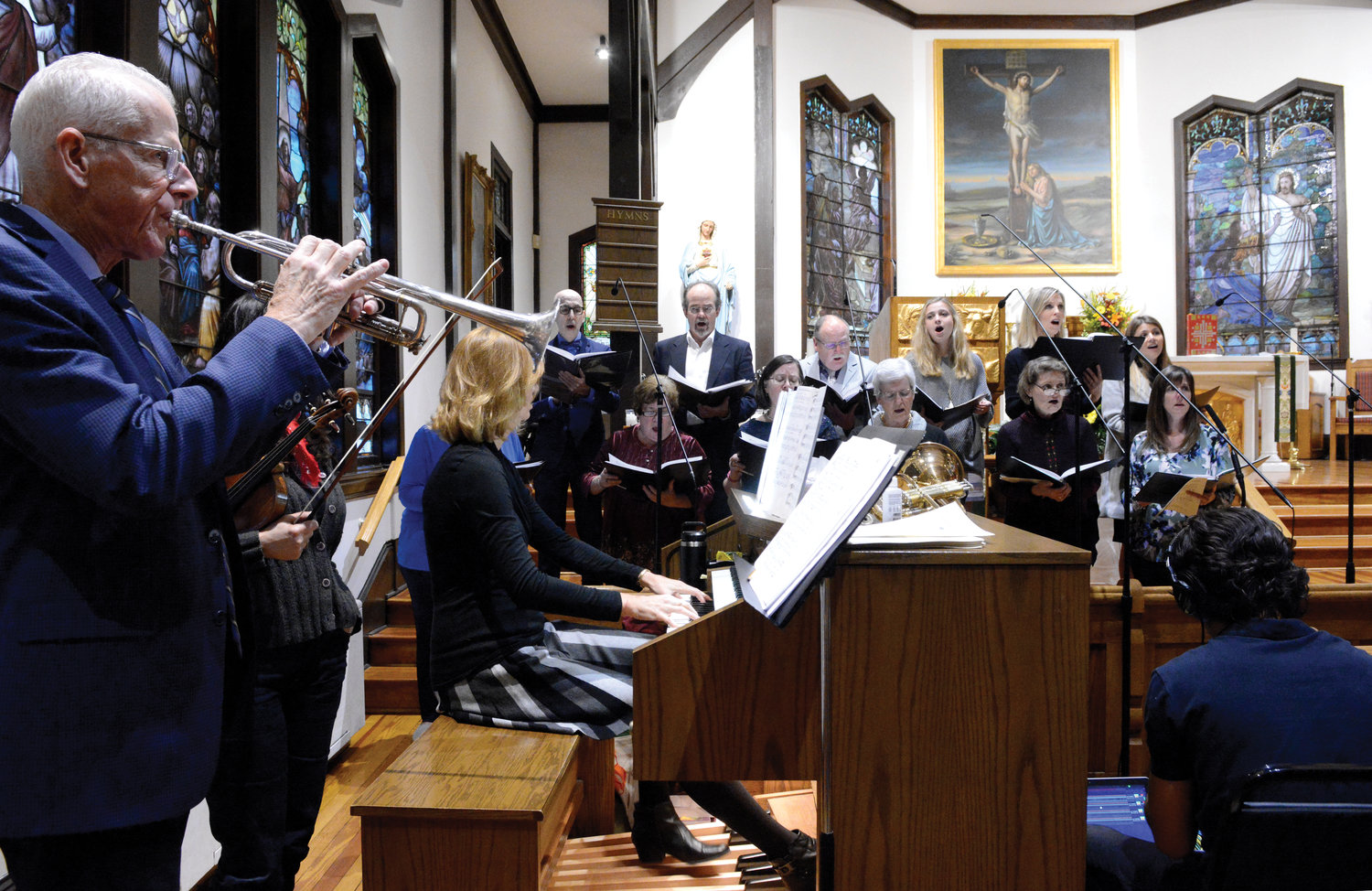 Anne Holland, parish director of music, plays the organ. Her husband, Jim Hughes, on the trumpet, and members of the parish choir join her.