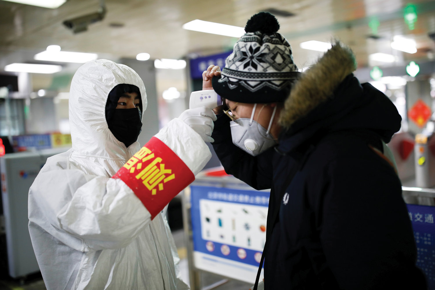 CAUTION—A staff member checks the temperature of a passenger entering a Beijing subway station Jan. 28 as the country is hit by an outbreak of the new coronavirus.