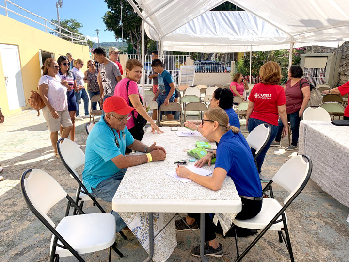 RECOVERY ASSISTANCE—Staff from archdiocesan Catholic Charities and volunteers with Cáritas de Puerto Rico distribute cash gift cards Feb. 1 to residents in the town of Guanica, Puerto Rico. The distribution site was St. Anthony's parish. The two women seated at right are Talia Lockspeiser, chief operating officer of archdiocesan Catholic Charities, foreground, and Beatriz Diaz Taveras, executive director of Catholic Charities Community Services.