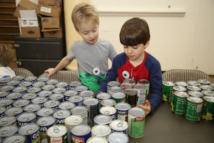 Luca Negron and Ollie Caputo organize cans of vegetables before the Children's Food Pantry opens at Ascension parish in Manhattan Jan. 25.