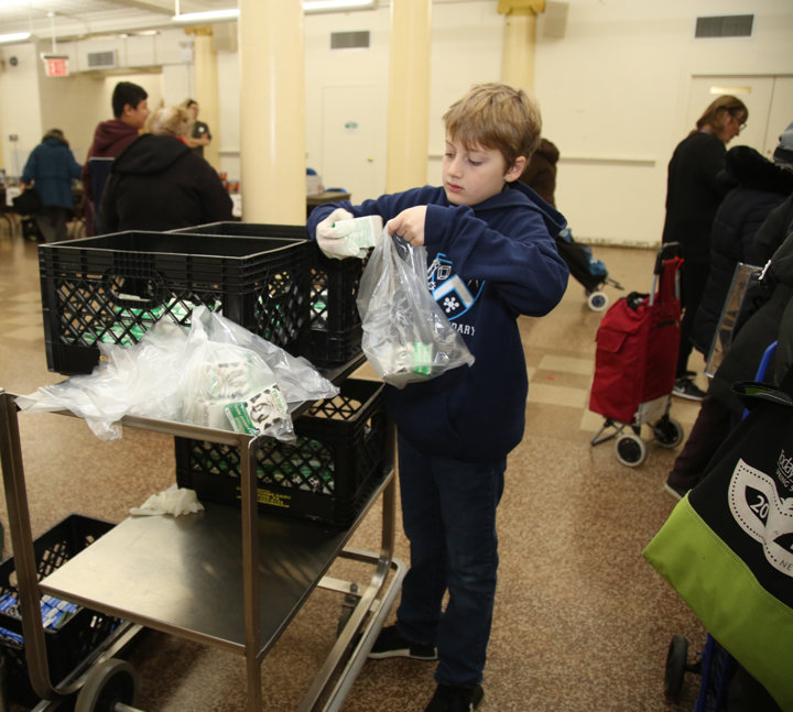 Jack van Schaik, a student in Ascension's religious education program, bags milk for the pantry.