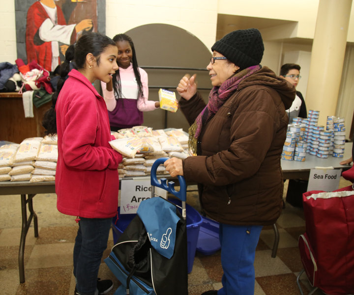 Ascension School students Reese Cordero and Kelly Awitor assist a shopper.