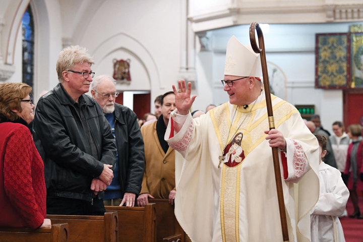 STEWARDSHIP ON STATEN ISLAND—Cardinal Dolan greets members of the congregation at Sacred Heart Church on Staten Island as he processes to the altar for the Vigil Mass he celebrated Feb. 1. At far left is Patricia Cowan, wife of Deacon James Cowan, a permanent deacon of Our Lady of Good Counsel parish on Staten Island who assisted with the Mass. A reception followed at Sacred Heart School for the Cardinal's Annual Stewardship Appeal (CASA) in the Staten Island Region.