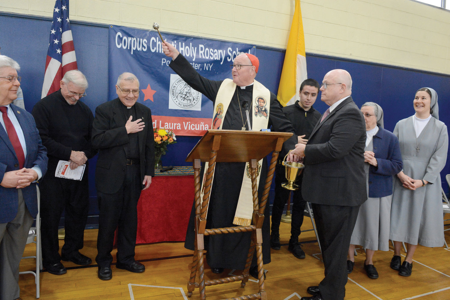 BLESSING—At a Jan. 31 gathering to celebrate the new universal pre-k program at Corpus Christi-Holy Rosary School in Port Chester, Cardinal Dolan blesses the Blessed Laura Vicuña campus and those attending the ceremony. Assisting was Michael Deegan, foreground, who is superintendent of schools in the archdiocese. The others, from left, are Port Chester Mayor Richard Falanka; Father John Grinsell, S.D.B., of St. John Bosco parish in Port Chester; Father Patrick Angelucci, S.D.B., pastor of St. John Bosco; Santiago Izquierdo, a seminarian from the Archdiocese of Philadelphia; Sister Lise Parent, F.M.A., school president; and Sister April Hoffman, F.M.A., second-grade teacher. There are 175 students and nine teachers in the all-day UPK program, which opened in September.