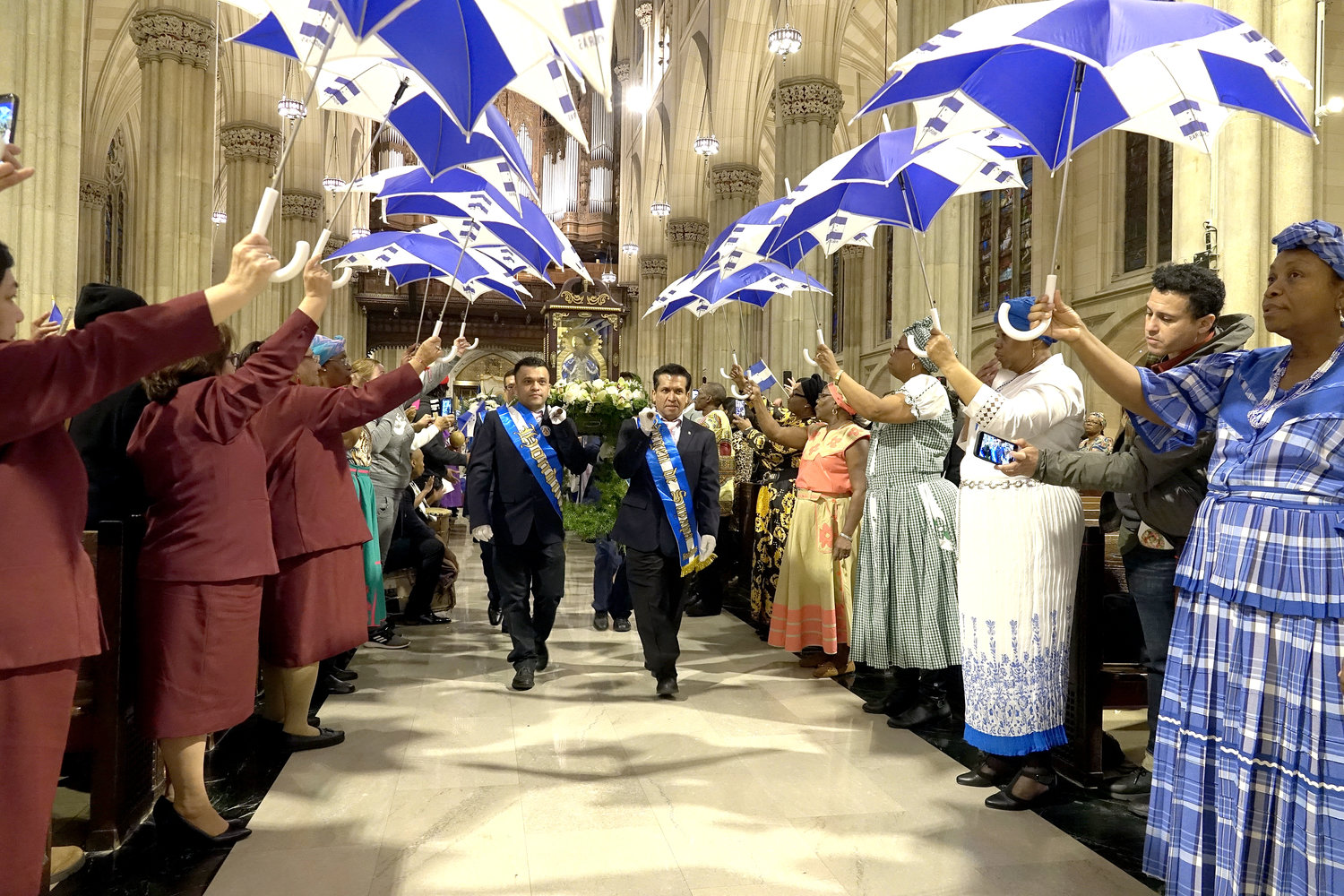 Participants in the entrance procession carry a figure of Our Lady of Suyapa up the center aisle of St. Patrick's Cathedral under a canopy of umbrellas Feb. 9 at the annual Mass in Spanish honoring the patroness of Honduras.