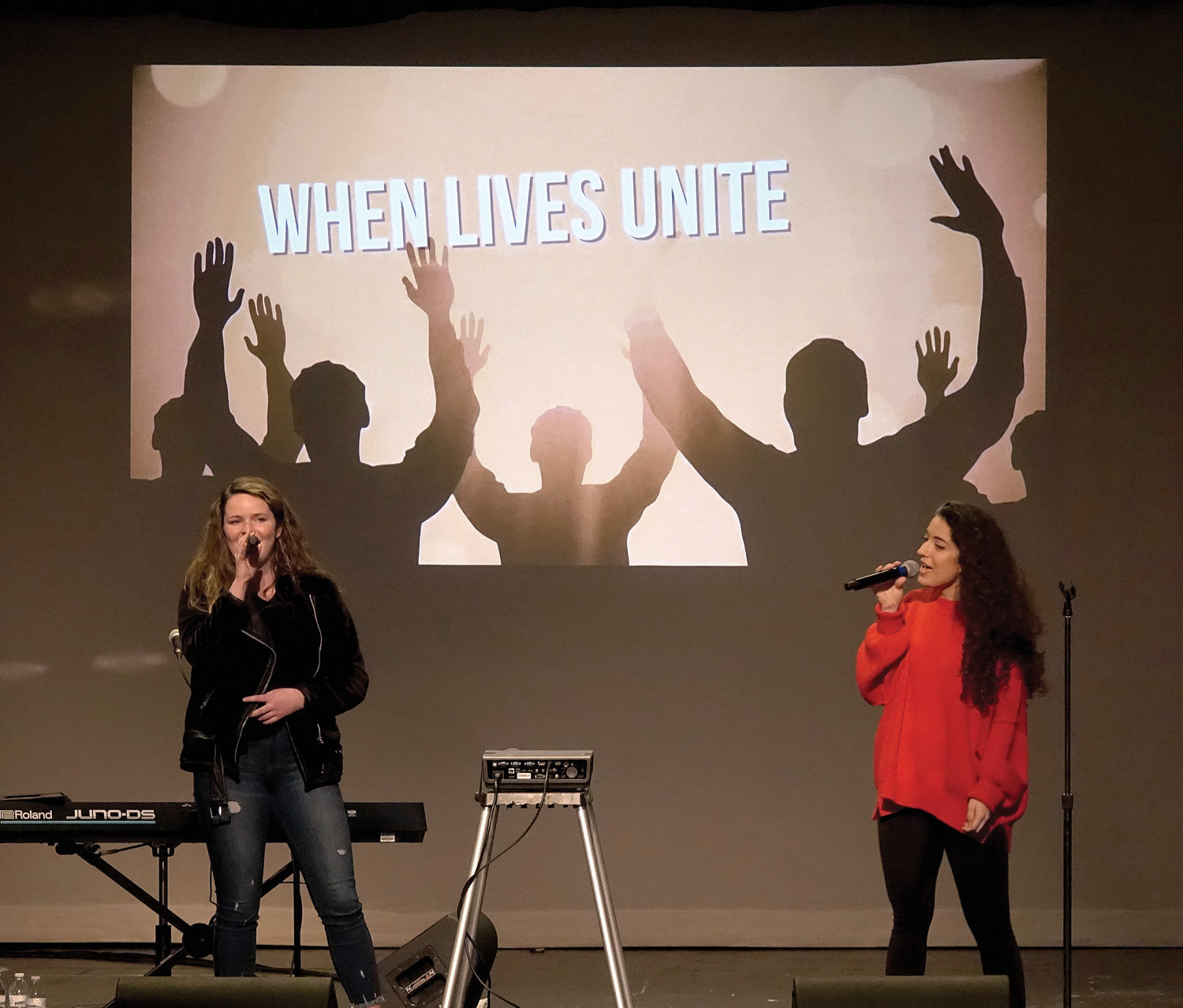Brianne Nealon, left, and Nicky Constabile, members of Array of Hope, sing during the retreat.