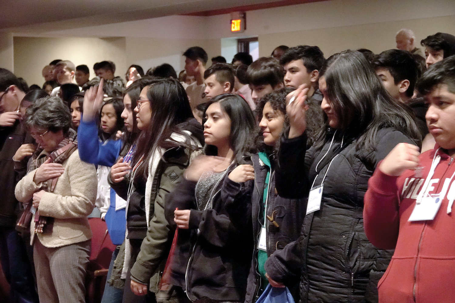 Students hold up their medals for a blessing by Auxiliary Bishop Gerald Walsh at a confirmation retreat at Archbishop Stepinac High School in White Plains Feb. 23.