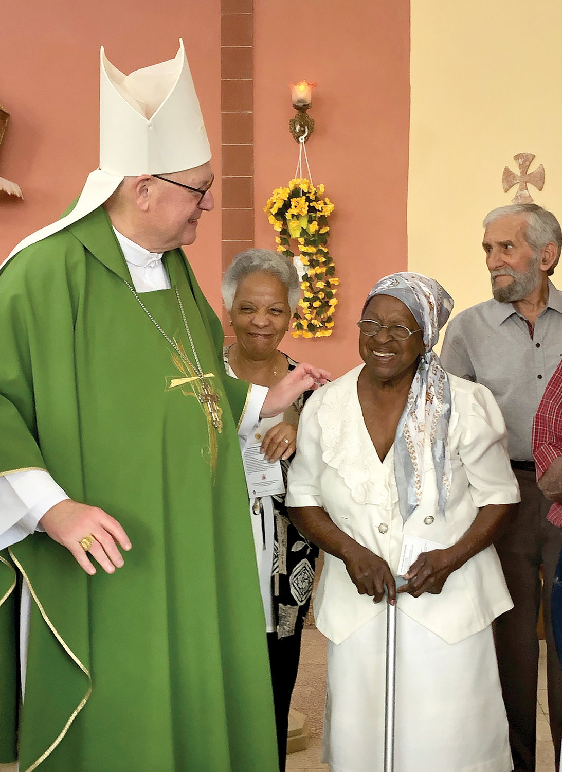 LIGHT MOMENT—Cardinal Dolan engages in friendly banter with residents of a home for the elderly in Camaguey, Cuba, after celebrating Mass there Feb. 9. The cardinal was in the midst of a six-day mission visit, his first on the island.