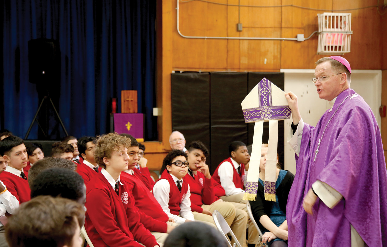 Bishop Whalen, holding up his miter, also gave a lesson to the freshman class about the vestments worn by bishops.