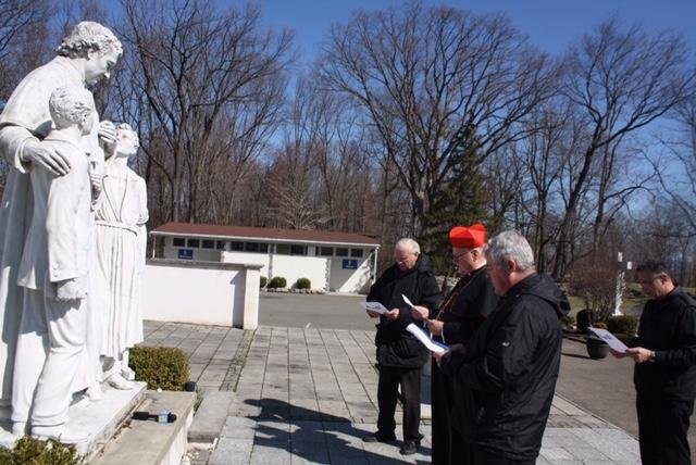 Cardinal Dolan prays with Salesian priests at a statue of St. John Bosco at the Shrine of Mary Help of Christians in Stony Point March 21. Flanking the cardinal were Father Stephen Ryan, S.D.B., left, and Father James McKenna, S.D.B.; standing in the back was Father Michael Pace, S.D.B.