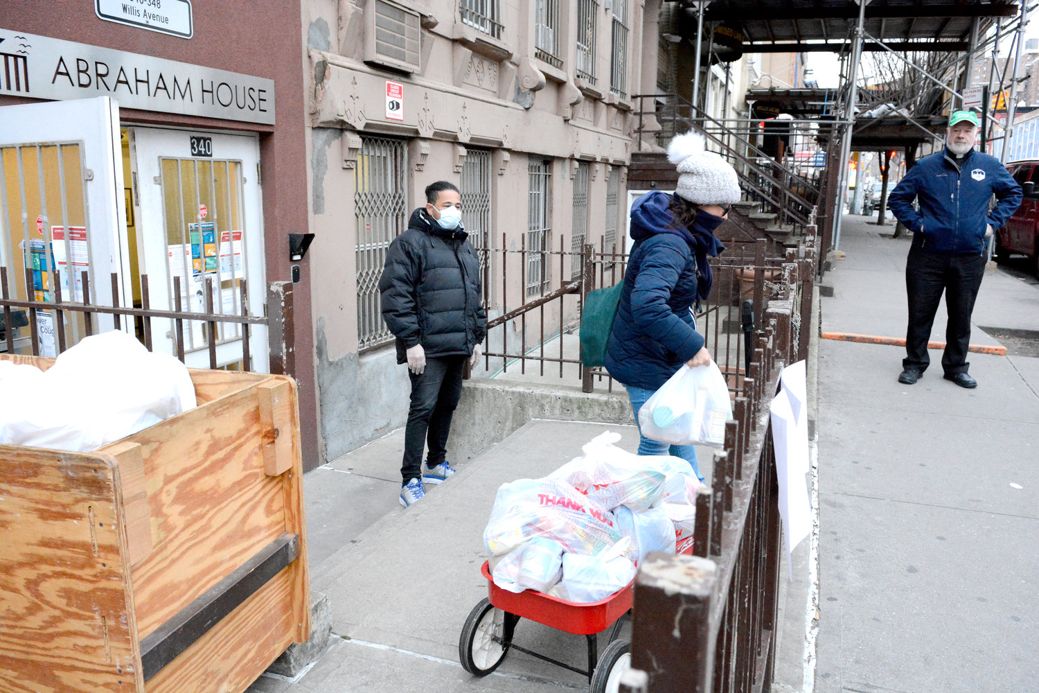 "OUTSIDE PANTRY—A woman carries a bag of food outside Abraham House in the Bronx, where a ""grab-and-go"" pantry was set up March 21. Looking on from the sidewalk was Msgr. Kevin Sullivan, executive director of Catholic Charities. Residential assistant Andres Fernandez, wearing mask, maintains proper social distancing."