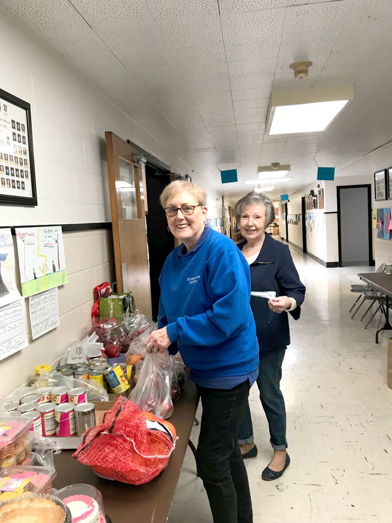 JOYFUL VOLUNTEERS—Diane Meleshkewich, front, and Sally O'Hara, both of whom are volunteers with the Tri-Parish Food Pantry based at St. Columba in Hopewell Junction, sort pantry items early last year.