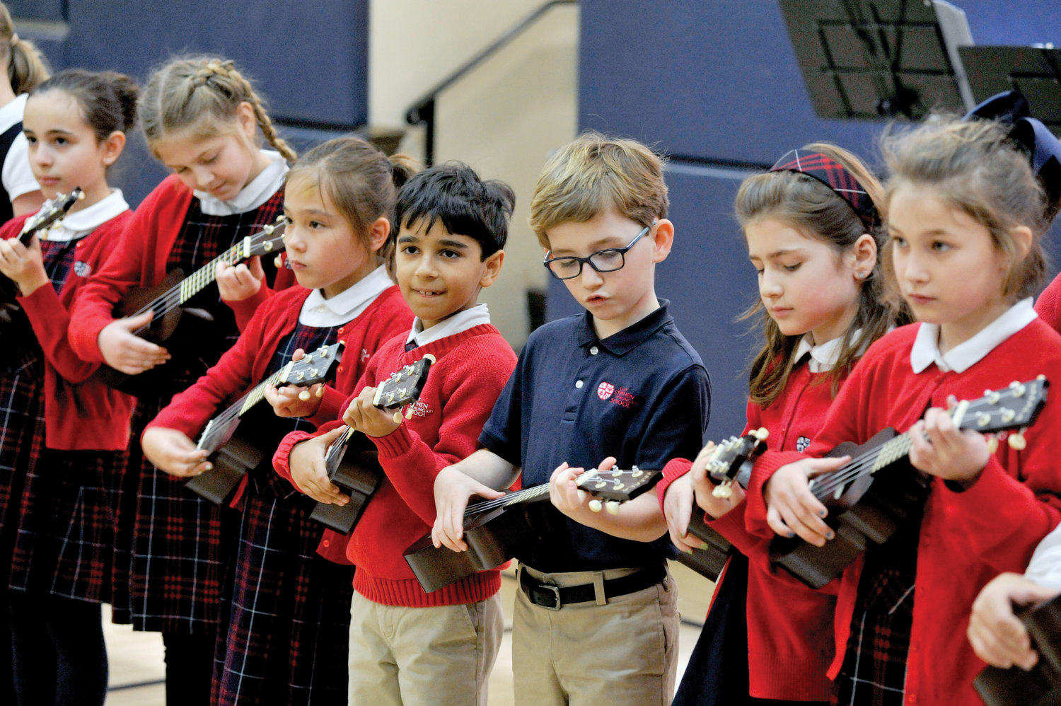 Youngsters play the ukulele during a reception.