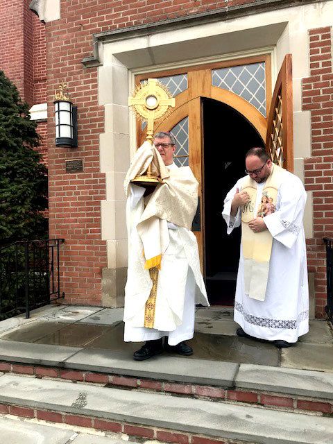 "BLESS AND PROTECT—Auxiliary Bishop Gerardo Colacicco, episcopal vicar for the Northern counties of the archdiocese, holds a monstrance containing the Blessed Sacrament outside the front door of St. Mary's Church in Wappingers Falls March 19, the feast of St. Joseph. At right is Father Justin Cinnante, O. Carm., making the sign of the cross. Bishop Colacicco, who is a priest in residence at St. Mary's, had requested pastors of Dutchess, Orange, Ulster and Sullivan counties also offer a simple Benediction with the Blessed Sacrament outside the front door of their churches at noon that day, invoking the blessing and protection of all their people against the spread of the coronavirus. ""Let our intention be the same: to seek God's mercy and forgiveness, to ask for Holy protection from the spread of the coronavirus and an end to this pandemic,"" he said in an email to them. ""How powerful a sign it will be if we all do this on the same day and at the same time. Even though our people cannot gather to be present, it is our hope that it will bring them comfort knowing that this was done by their priests."""