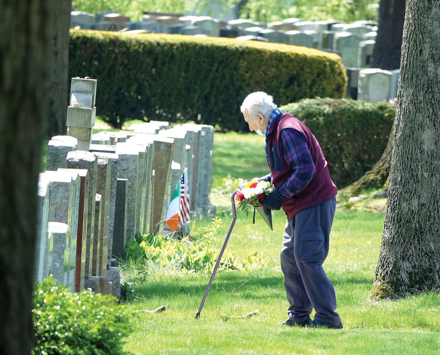 An older gentleman carefully cradles a bouquet of flowers to be placed at a gravesite on Mother's Day, May 10, at Gate of Heaven Cemetery in Hawthorne.