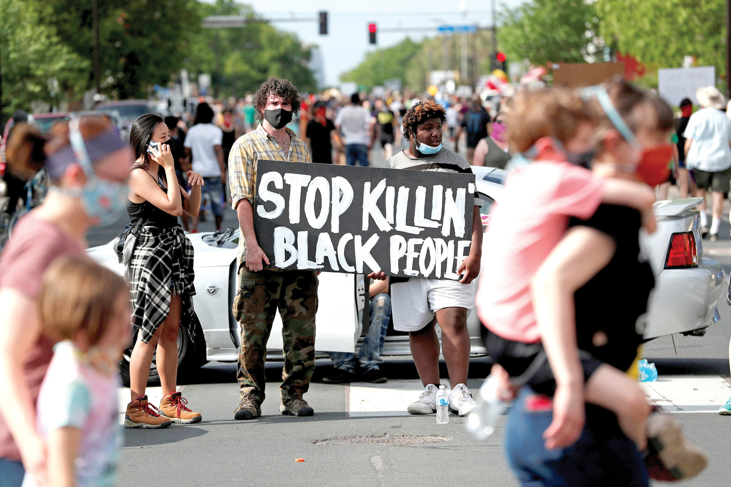 Protesters in Minneapolis, top, gather at the scene May 27 where George Floyd, an unarmed black man, was pinned down by a police officer kneeling on his neck and was later declared dead at a hospital May 25.