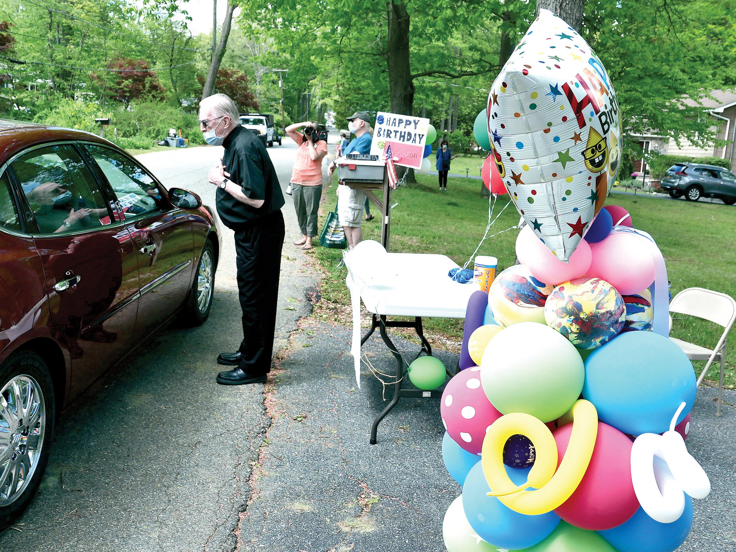 Msgr. Dermot Brennan, the beloved pastor emeritus of St. Patrick's parish in Yorktown Heights, receives guests at his surprise 90th birthday car parade outside a house of a former parishioner on Gregory Street in Yorktown Heights. A long line of cars traversed the parade route. Festive balloons and creative, homemade signs made colorful party props.