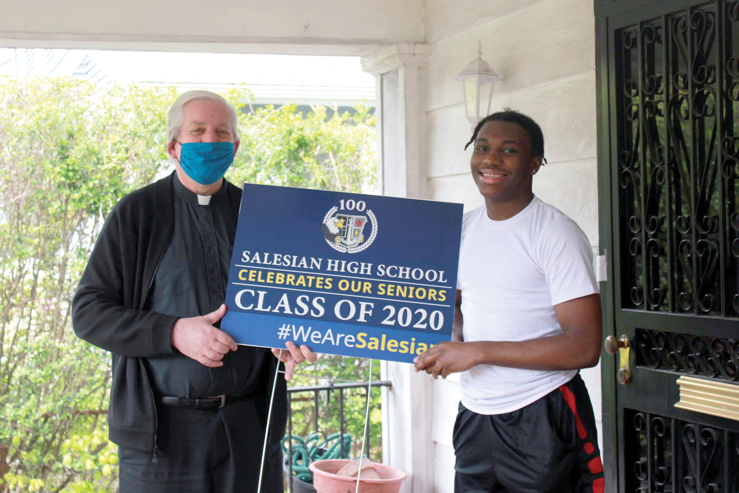 PRESIDENTIAL VISIT—Father John Serio, S.D.B., presents a Salesian High School Class of 2020 lawn sign to senior Elijah Woods. Father Serio, president of Salesian High School, delivered the lawn signs over an 11-day period to the homes of Salesian's graduating seniors, who have not attended class in the New Rochelle school building since March 12 due to the coronavirus pandemic.