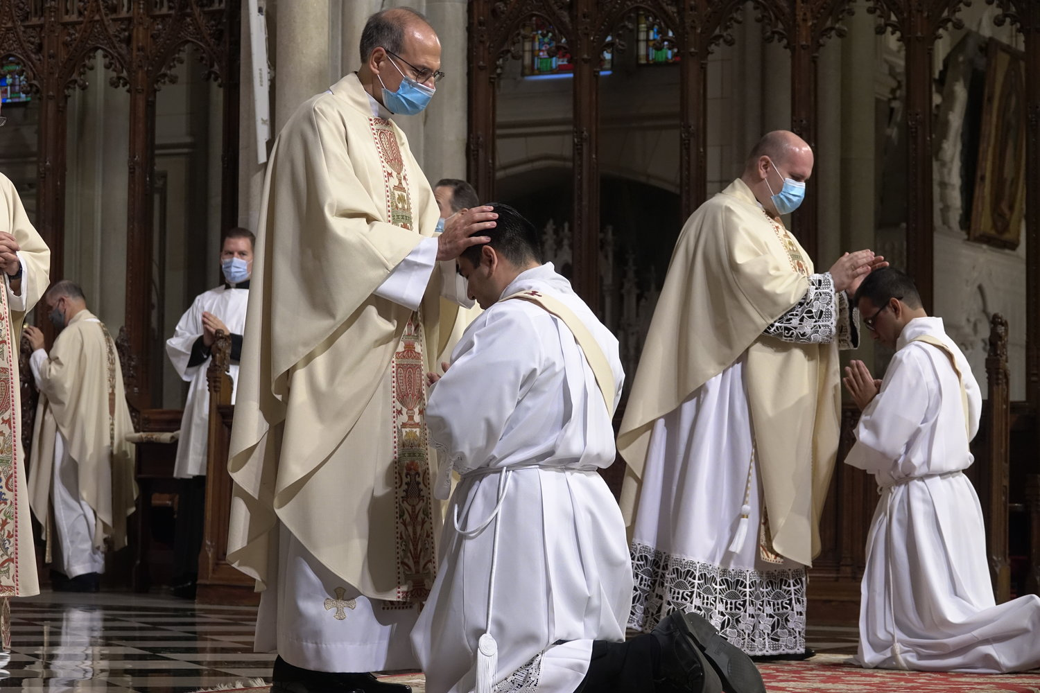Priests lay hands on the heads of their new priestly brothers.