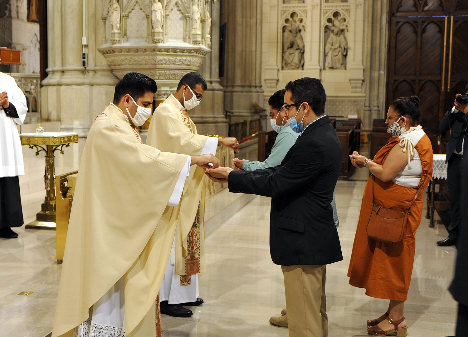 The two new priests distribute Communion to the faithful.