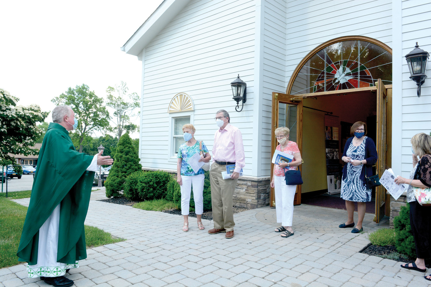 Father Michael Keane, pastor of St. Anastasia, greets parishioners outside after Mass.
