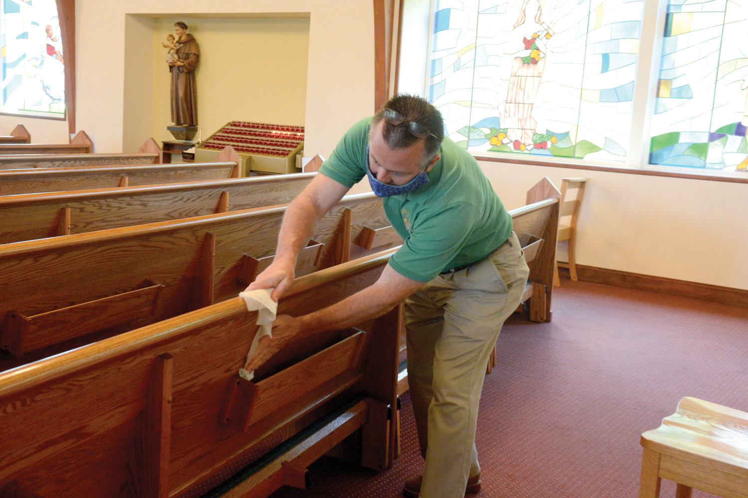 Usher Jim Banville wipes down a pew following Mass.