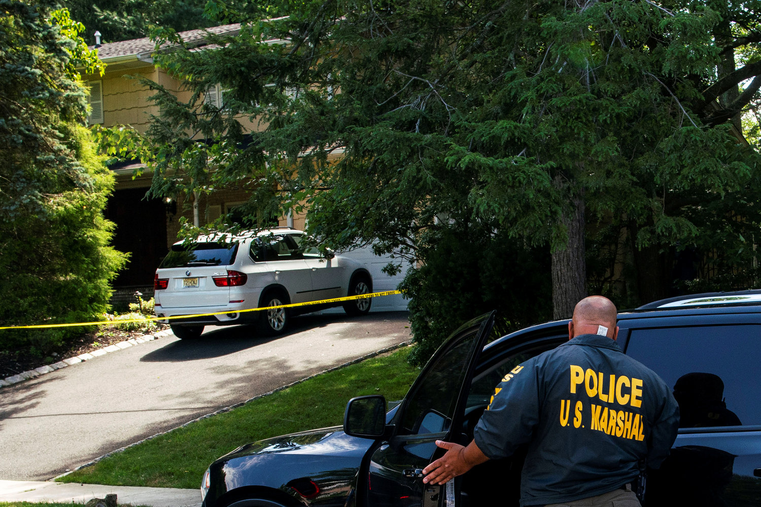 Law enforcement officials in North Brunswick, N.J., are seen outside the home of federal Judge Esther Salas July 20, where her son was shot and killed and her husband was critically injured the day before.