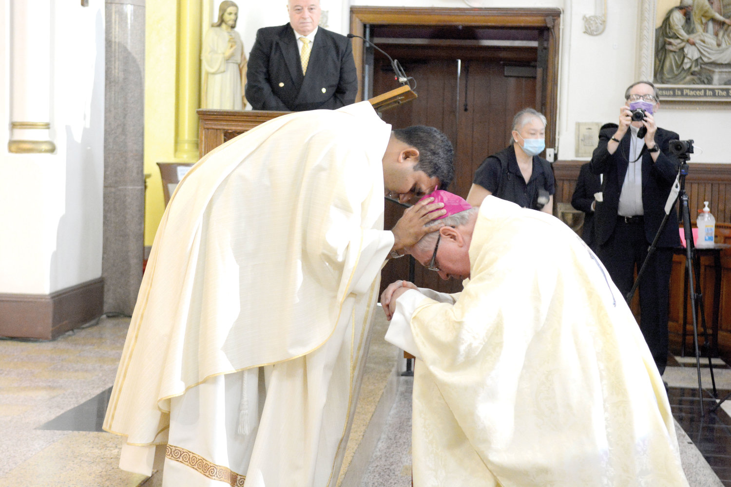 Father Lokuhettige offers a first blessing to Bishop O'Hara.