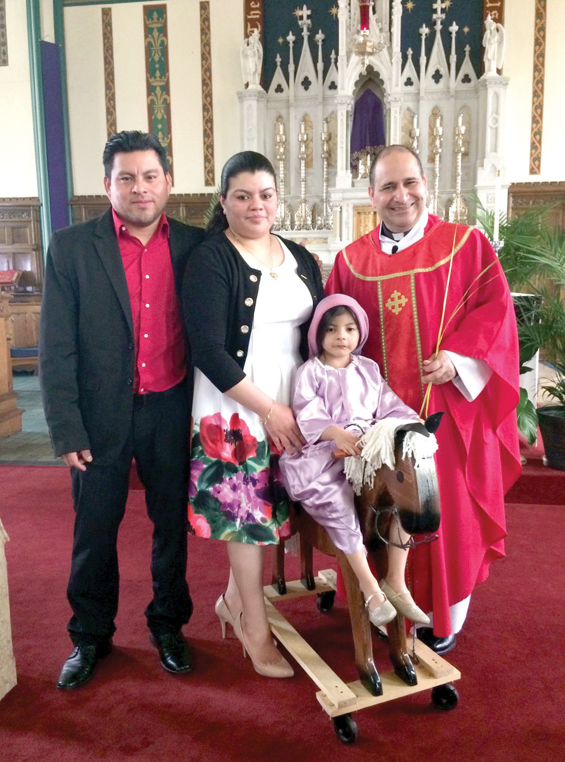 IN CHURCH—Father Pichardo greets parishioners Freddy and Veronica Baide and their daughter Katie after a Mass last December at St. Mary-St. Peter parish in Kingston.