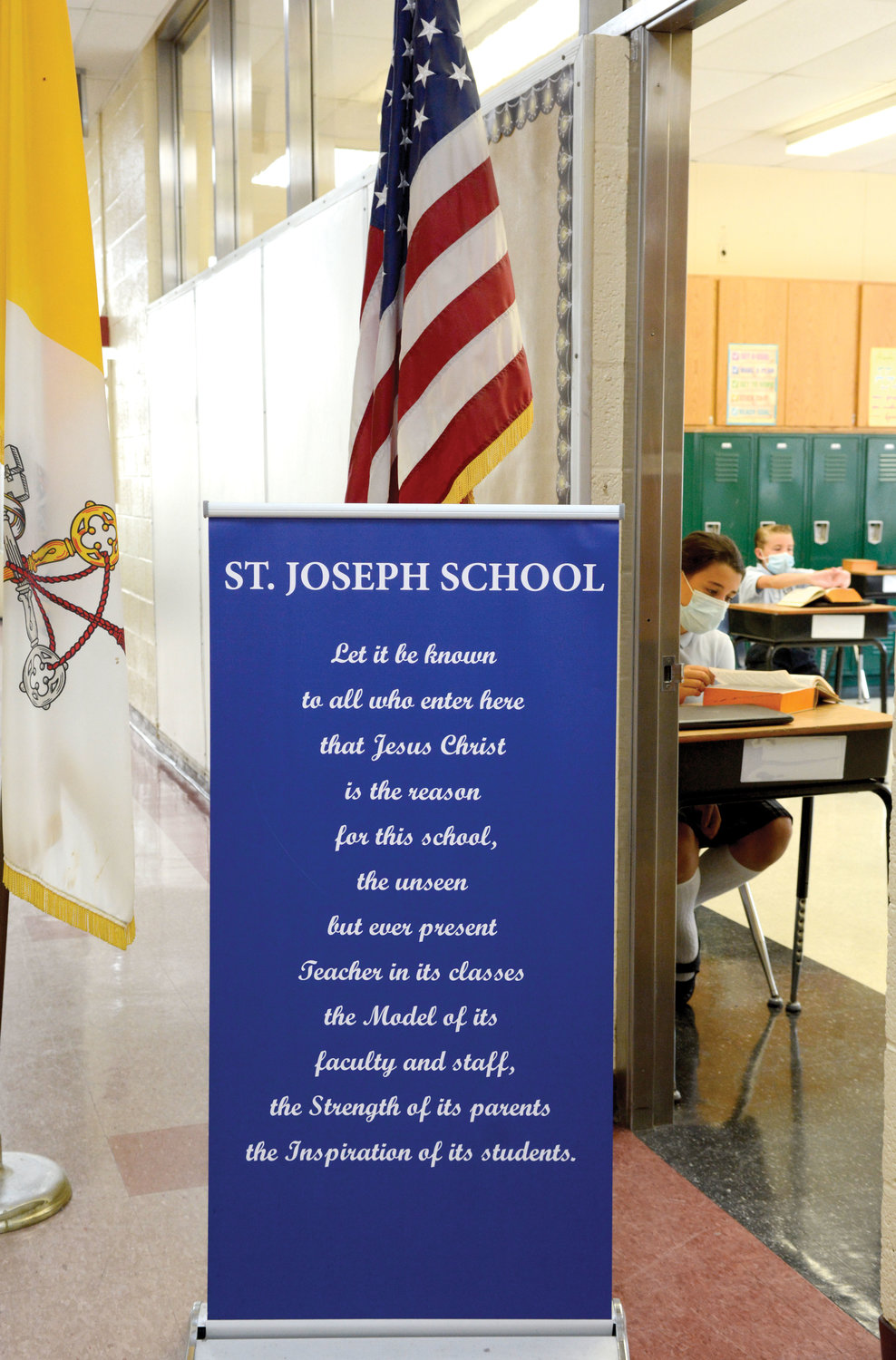 The school's adherence to Catholic identity is showcased through an inspirational banner placed near the Vatican and American flags.