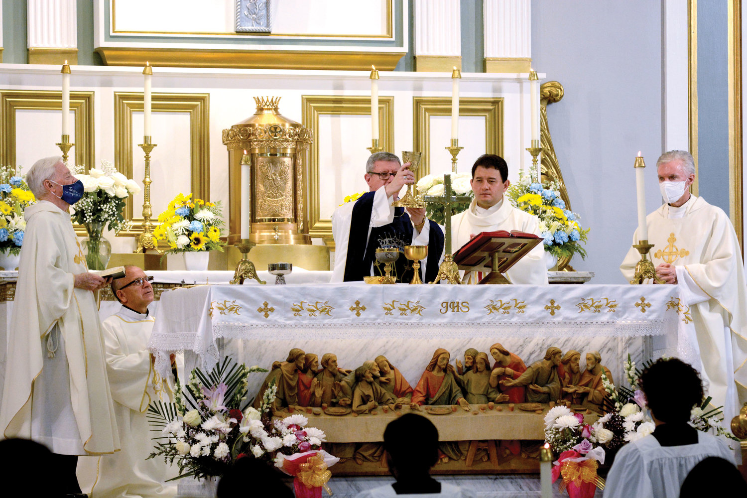 SACRED MOMENT—Auxiliary Bishop Gerardo J. Colacicco lifts the chalice during the consecration at the Vigil Mass for the feast of the Assumption of the Blessed Virgin Mary Aug. 14 at Assumption parish in Peekskill. On the altar with the bishop are, from left,