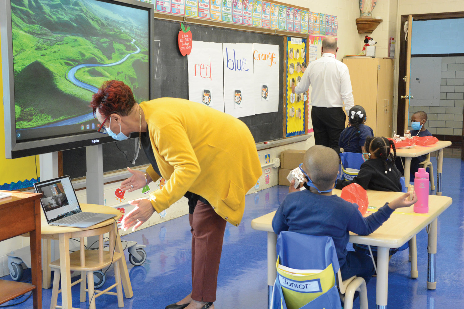 Kindergarten teacher Estoria Wills teaches students on Zoom Sept. 22. In the background assisting students is principal Rich Helmrich.