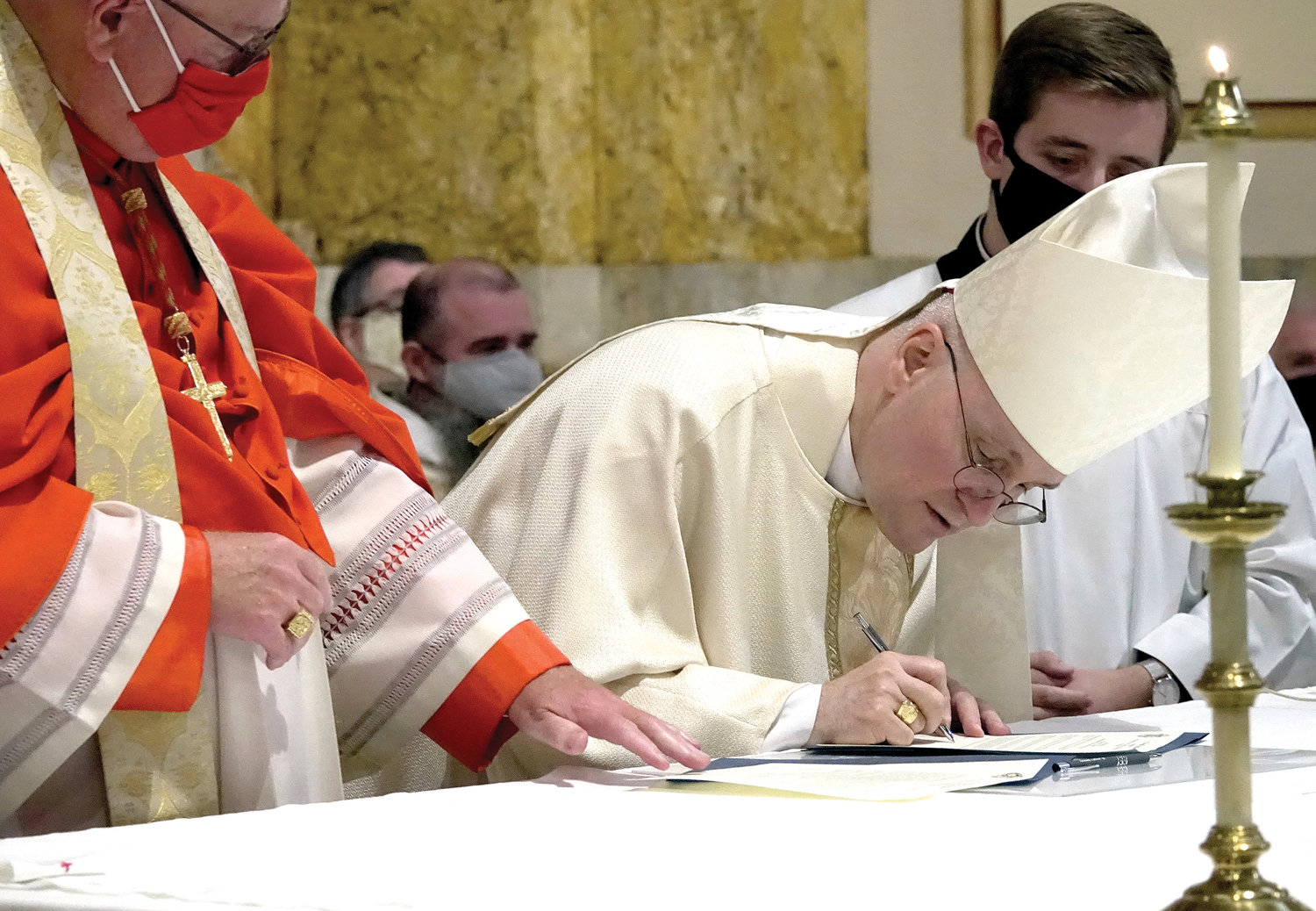 Auxiliary Bishop James Massa of Brooklyn signs oath of fidelity before Cardinal Dolan at the Sept. 13 Mass in which the bishop was officially installed as rector of St. Joseph's Seminary, Dunwoodie.