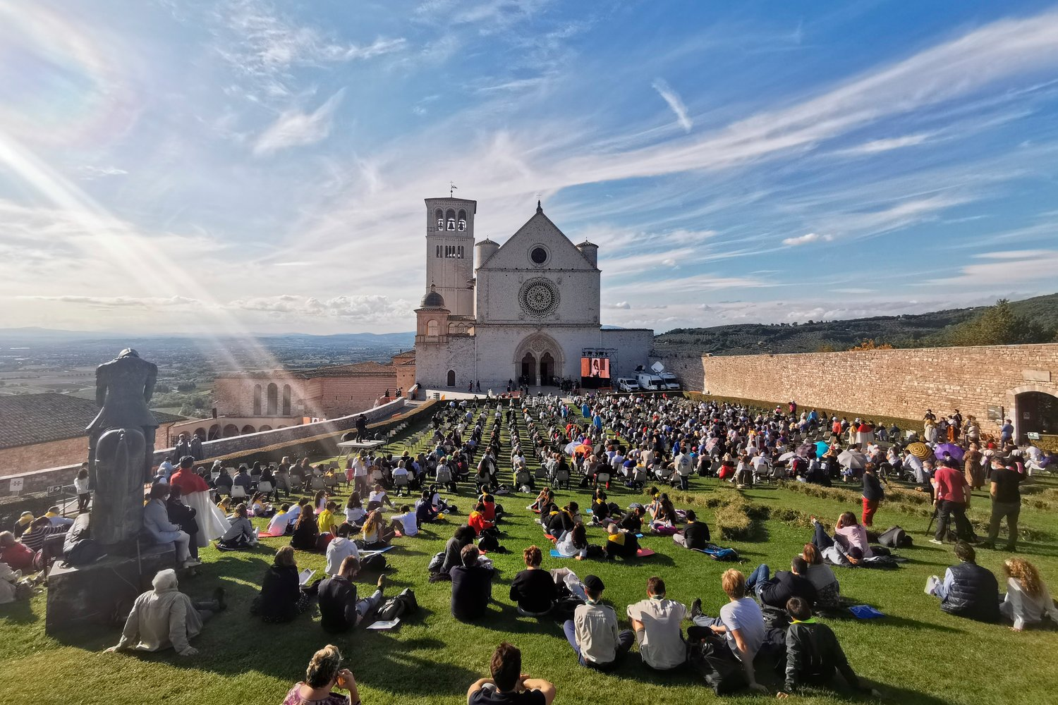 People sit outside the Basilica of St. Francis in Assisi as they attend the beatification Mass of Carlo Acutis in Assisi, Italy, Oct. 10. The Mass was held inside the basilica but measures to prevent the spread of Covid-19 meant that most of the attendees sat outside.