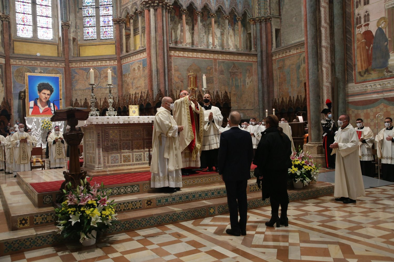 Italian Cardinal Agostino Vallini raises a reliquary containing the heart of Carlo Acutis during his beatification Mass in the Basilica of St. Francis in Assisi in Assisi, Italy, Oct. 10. The reliquary was presented by the beatified teen's parents, Andrea Acutis and Antonia Salzano, pictured standing in front of the altar.