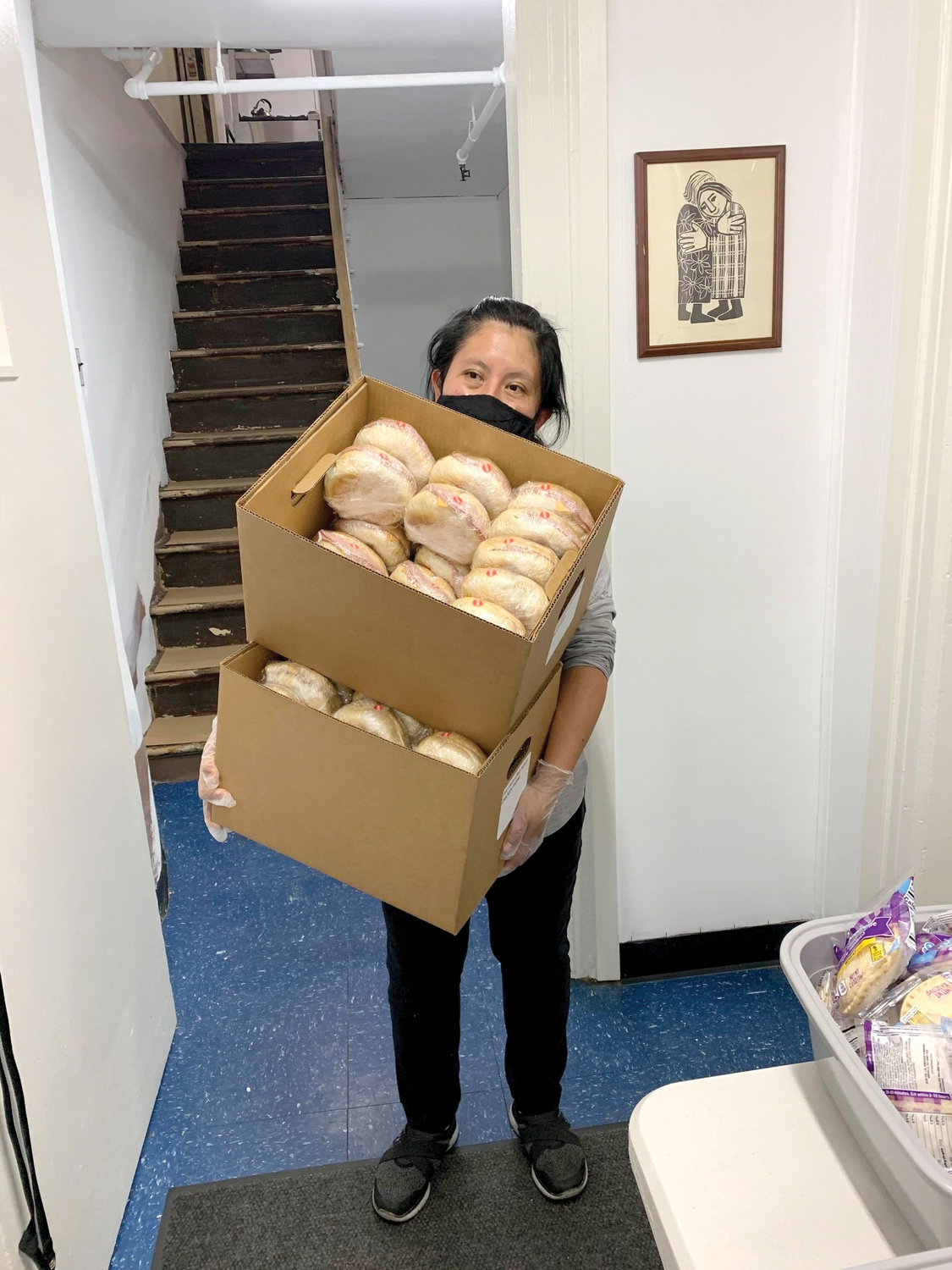 COMMUNITY DINNER—Luisa Mendez-Vega, a 20-year staff member of The Dwelling Place of New York, carries boxes of sandwiches for distribution at a Wednesday take-out dinner for former residents as well as members of the local community. The Manhattan women's shelter, which was forced to temporarily shut its doors in June, is planning to reopen in early January.