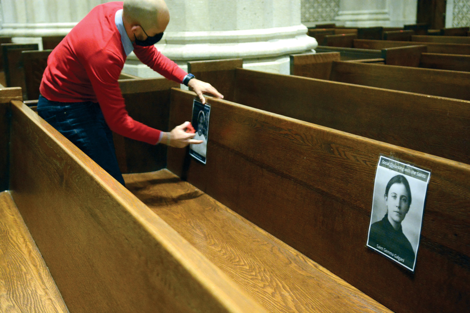 Images of saints are placed in the pews to designate where young adults were permitted to sit in observance of proper social distancing.