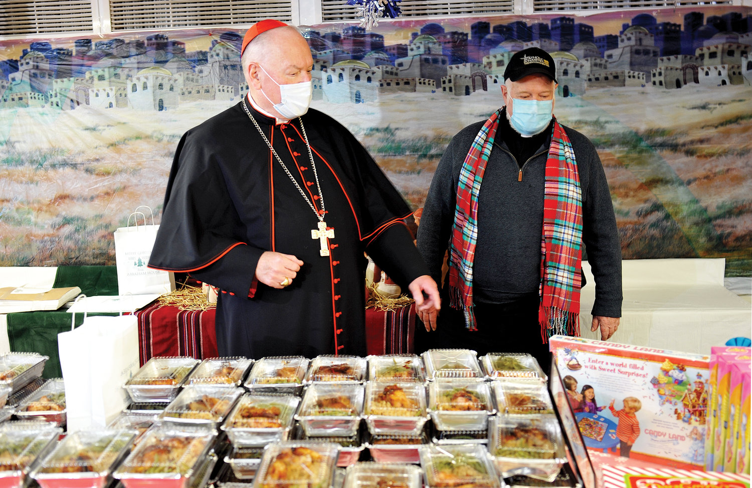 At Abraham House Dec. 22 in the Mott Haven section of the Bronx, Cardinal Dolan and Msgr. Kevin Sullivan, executive director of archdiocesan Catholic Charities, stand near the food provided through Abraham House, an affiliate of Catholic Charities.