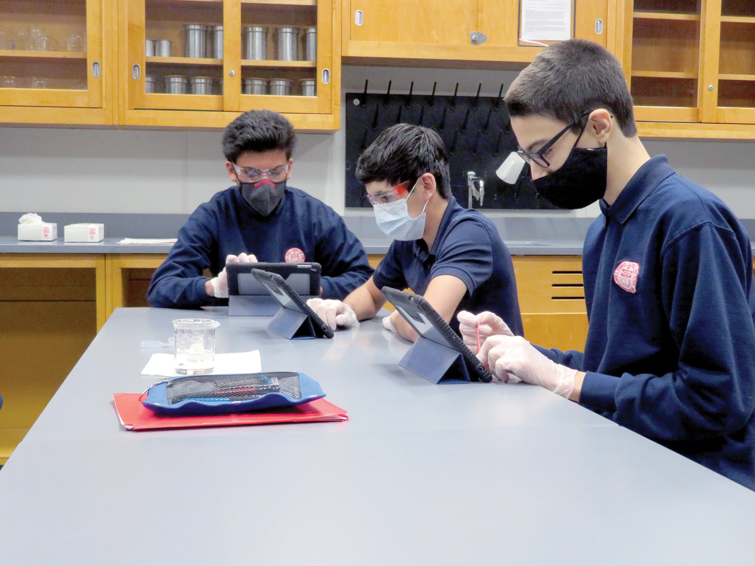Students at John F. Kennedy Catholic Preparatory School in Somers are divided into two cohort groups that alternate weeks of in-person study with virtual instruction at home. Sophomores Jalen Alvarez-Vasquez, Ellis Kennedy and Lukas Gojcaj complete a solubility chemistry laboratory experiment.