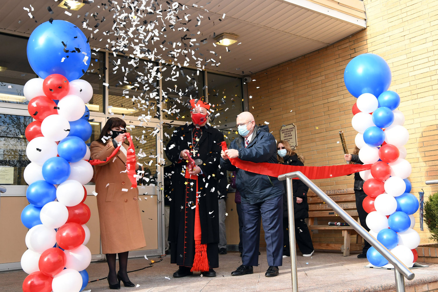 Cardinal Dolan cuts the ribbon at the dedication, assisted by Zoilita Herrera, regional superintendent of Staten Island Catholic schools, left, and Michael Deegan, superintendent of schools in the archdiocese, right.