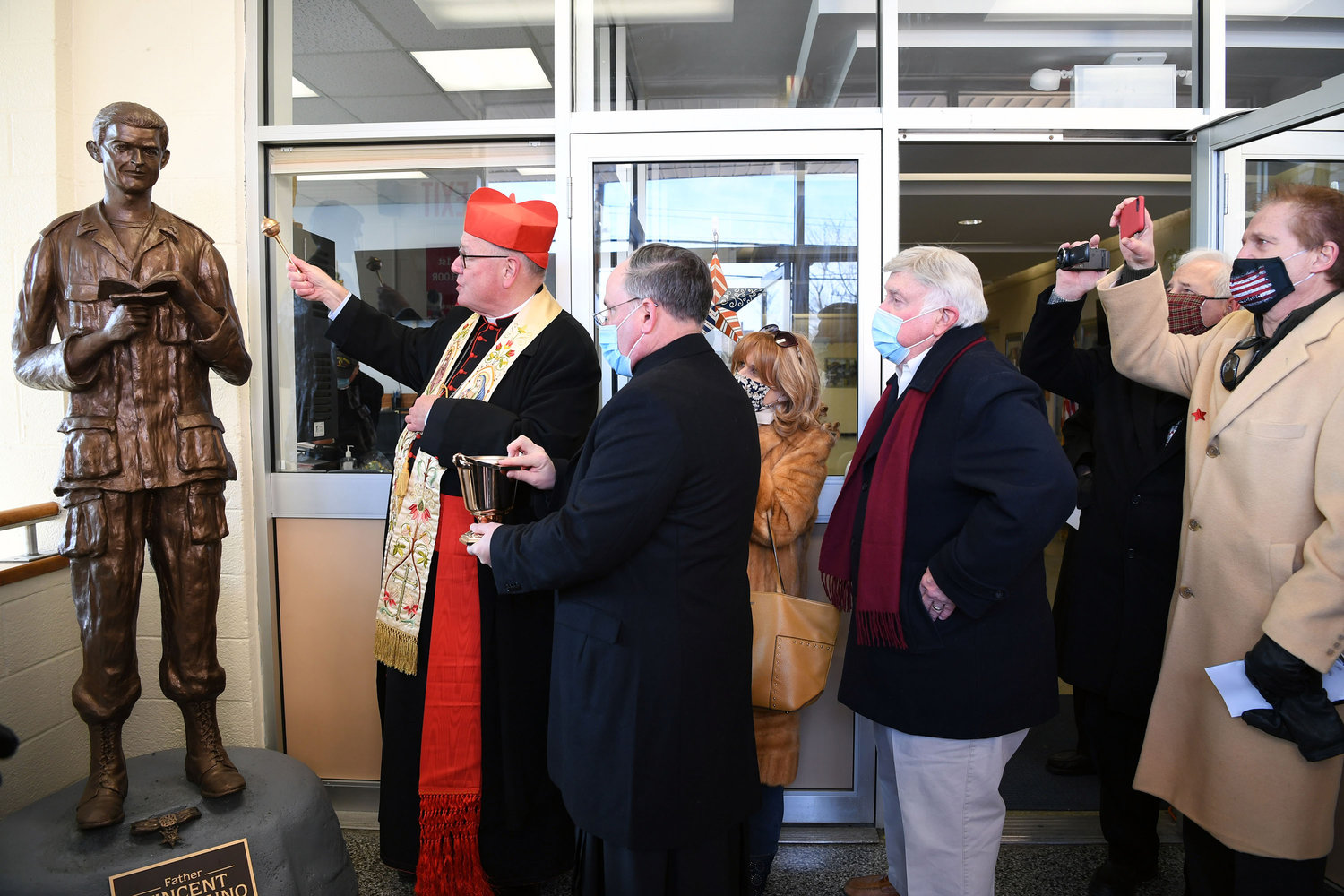 Cardinal Dolan blesses a statue of Father Vincent Capodanno, M.M., in the lobby of Father Vincent Capodanno Catholic Academy on Staten Island Jan. 21. Cardinal Dolan, who dedicated the academy in the same ceremony, is assisted by Father Michael Martine, pastor of Holy Rosary parish on Staten Island. The academy opened in September after the merger of Holy Rosary and St. Adalbert schools for the 2020-2021 school year.