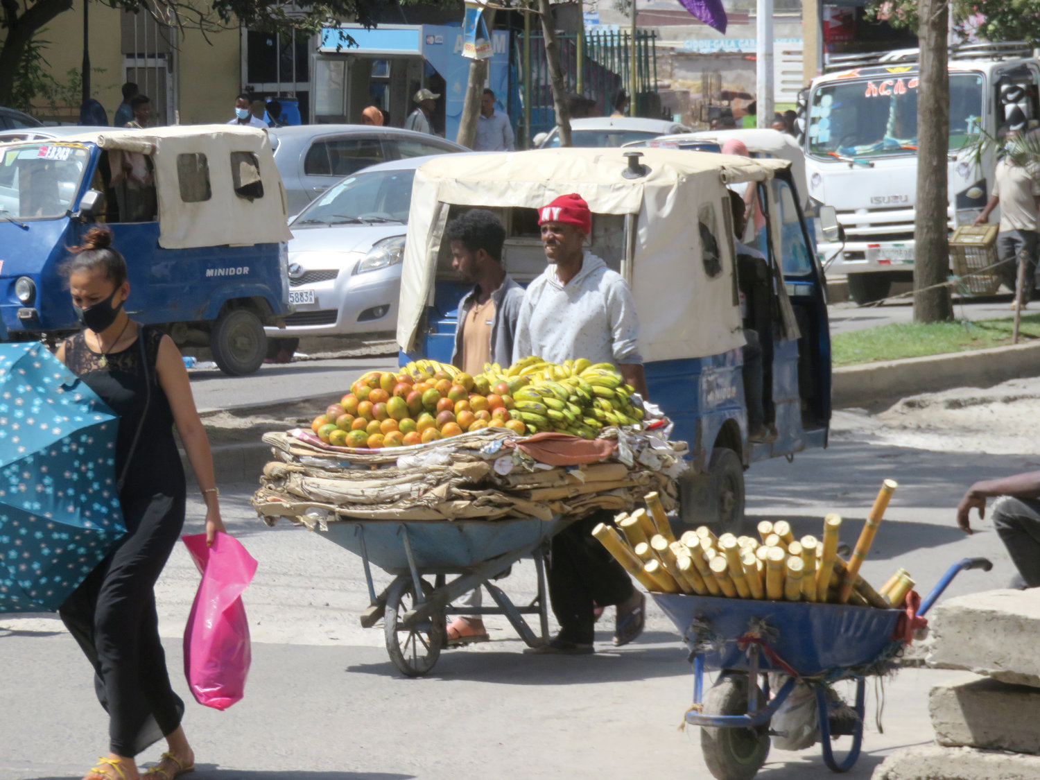 A local vendor wearing a New York hat pushes a cart with fresh produce.