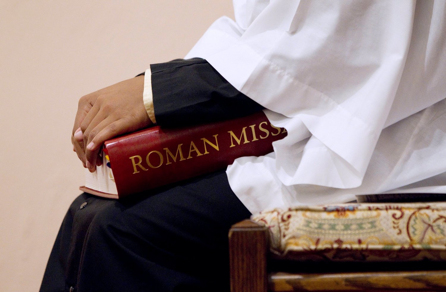 An altar server holds a copy of the Roman Missal during Mass at St. Joseph Catholic Church in Alexandria, Va., in this 2011 file photo.