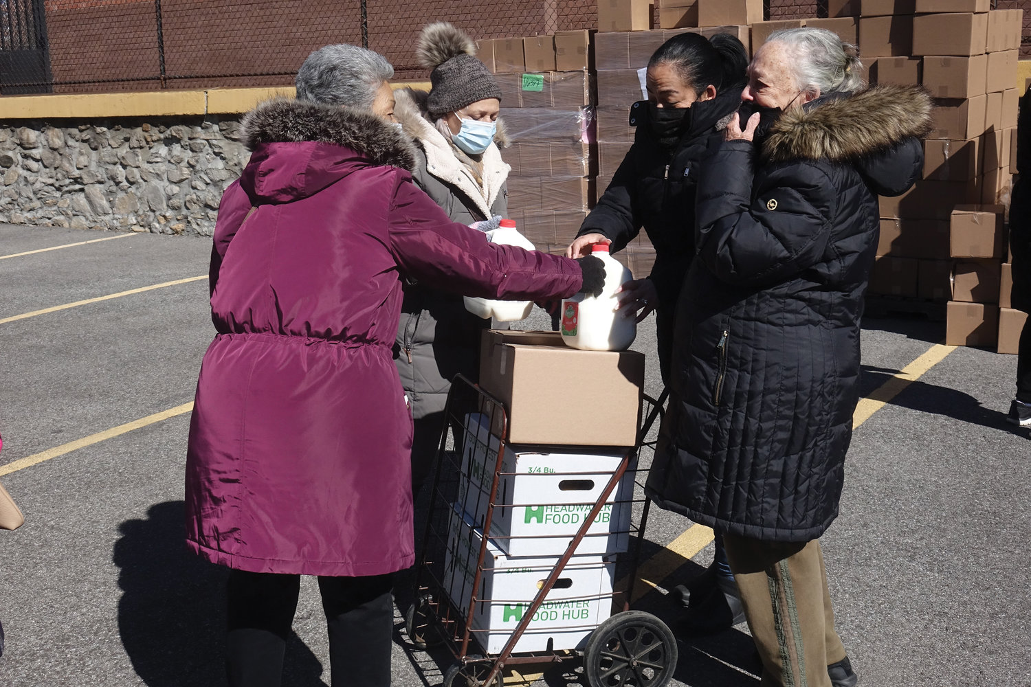 Grateful recipients are shown with food donations.