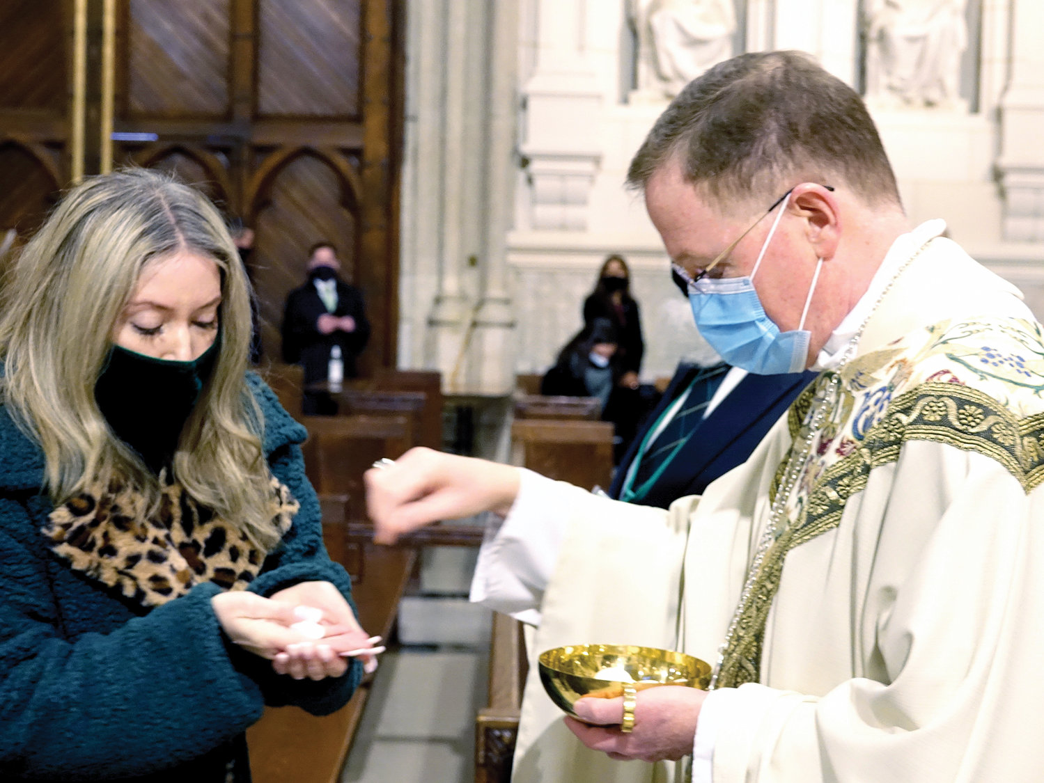 Auxiliary Bishop Edmund Whalen distributes the Eucharist during the morning liturgy. The bishop was cited as part of the parade's first-ever honor guard of first responders and essential workers.