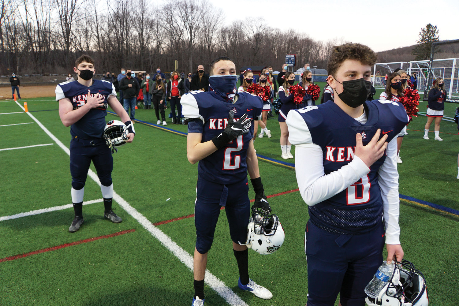 Bobby Piesco, Francisco Rivera and Carmine Calandrello stand for the National Anthem before John F. Kennedy Catholic Preparatory School and St. Dominic High School kicked off the football season in Somers March 12.