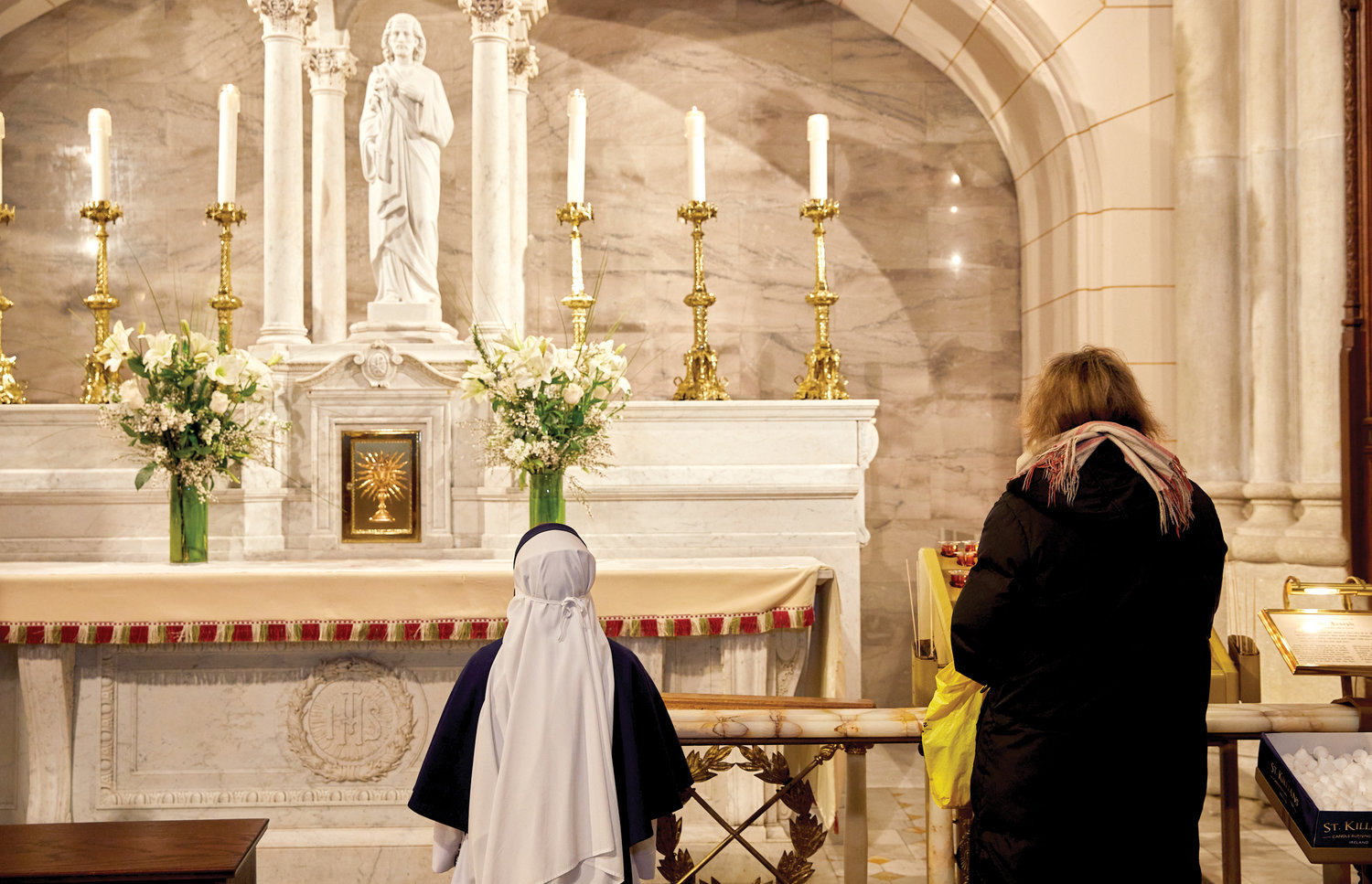 A Sister of Life kneels before the statue of St. Joseph that graces the side altar of the saint at St. Patrick's Cathedral March 19. Cardinal Dolan had just consecrated the Archdiocese to St. Joseph following the 7 a.m. Mass he offered at the cathedral's main altar.