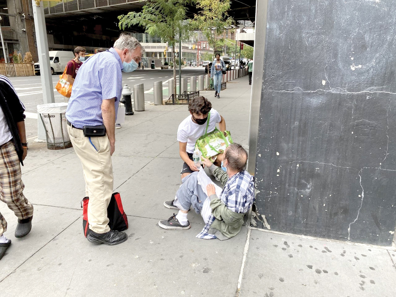 Ed Greene, left, co-pastoral director of LAMP, and NYU freshman Luis Gonzalez provide assistance to a man in Manhattan.