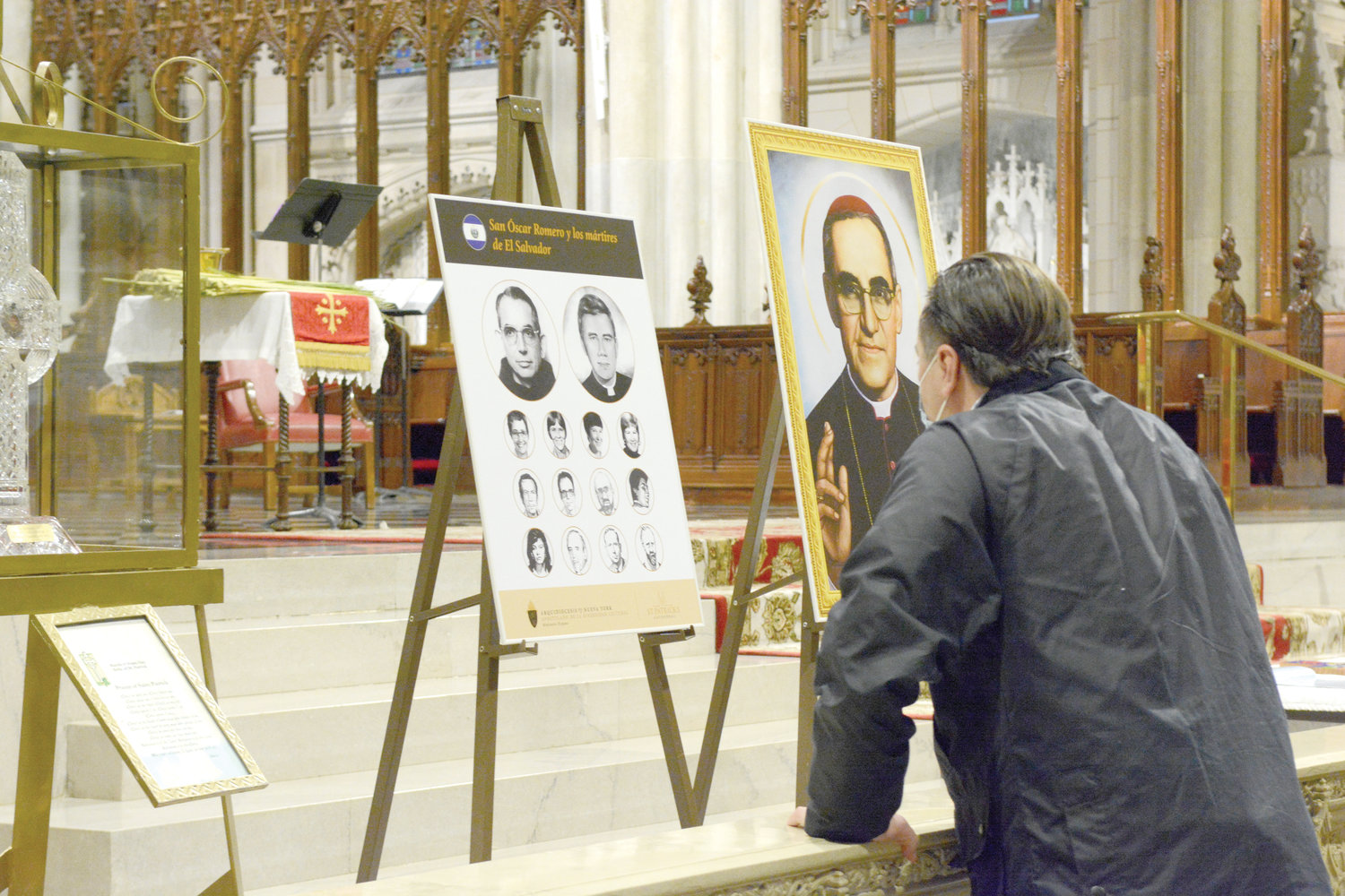 A man observes an altar-steps display March 28 before a Mass honoring St. Oscar Romero at St. Patrick's Cathedral. St. Romero, assassinated March 24, 1980, was archbishop of San Salvador. The Palm Sunday Mass was also offered in honor of the Martyrs of El Salvador. Auxiliary Bishop Luis Romero Fernandez of Rockville Centre served as principal celebrant and homilist.