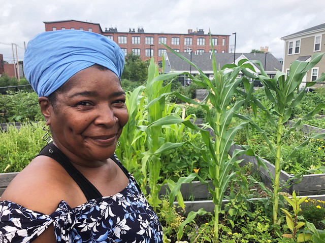 Raffini, a black storyteller and a resident of the Sankofa apartment complex, proudly stands in front of her raised growing bed.